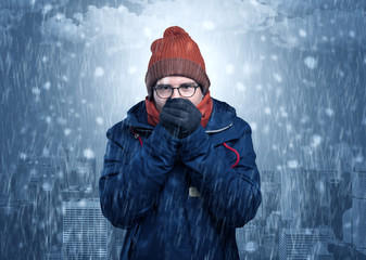 Boy freezing in cold weather with city concept