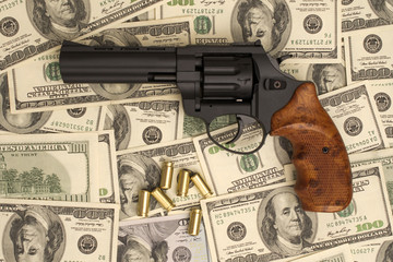 pistol with ammunition against the background of dollars