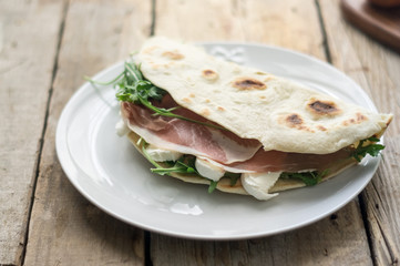 Homemade Italian flatbread called piadina with rocket salad, prosciutto and ricotta cheese.