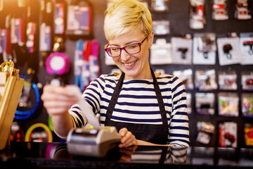 Beautiful cheerful woman while pulling out a check from the cashier. Wall mural