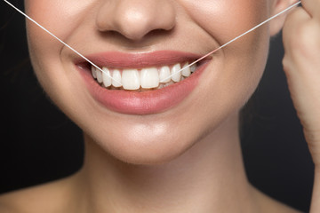 Dental health concept. Close up of mouth of cheerful girl who is cleaning his teeth by special thread. Isolated on dark background