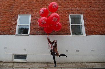 Women holds balloons at anti-Putin protest outside the Russian Embassy in London