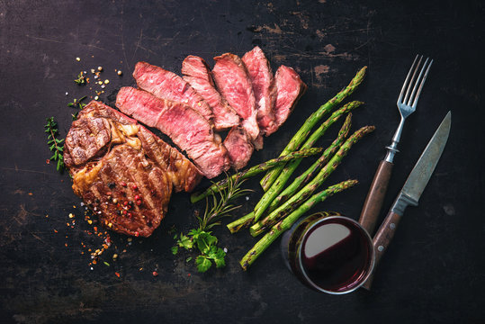 Roasted rib eye steak with green asparagus and wine