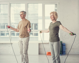Smiling old woman and gentleman jumping with skipping ropes at fitness studio