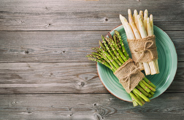 Bunches of fresh green and white asparagus on wooden background