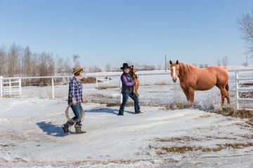 two cowgirls walking with saddle toward horse to saddle up