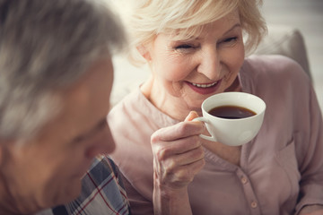 Delighted female pensioner enjoying hot drink while sitting with her husband inside. Focus on granny