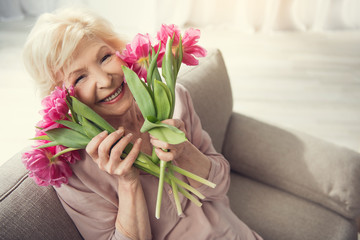 Elderly female person sitting at home with tulips and looking at camera with bliss. Copy space in right side. Top view