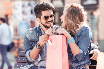 Portrait of smiling young couple resting after shopping.