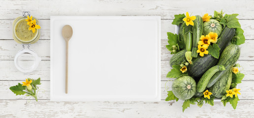 zucchini, flowers and green sauce in glass jar food top view, isolated on wooden table with white cutting board in kitchen worktop