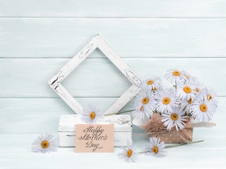 Mother's day theme. Chamomile, greeting card, casket and vintage photo frame  on wooden background in Shabby Chic style. Celebratory interior. Place for photo or text.