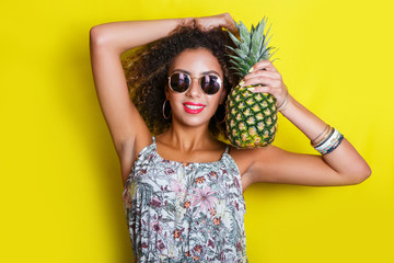 Fashion summer portrait smiling afro american girl in sunglasses and pineapple over yellow background