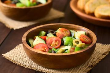 Frischer bunter Salat aus Oliven, Kirschtomaten, grünem Paprika und Gurke, fotografiert mit natürlichem Licht (Selektiver Fokus, Fokus in die Mitte des Salats)