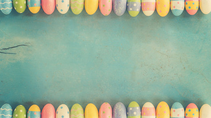 Colorful easter eggs on wooden pastel color background with space.