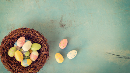 Colorful easter eggs in nest on wood pastel color background with space.