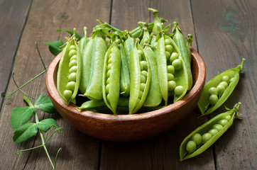 Pods of green peas in wooden bowl