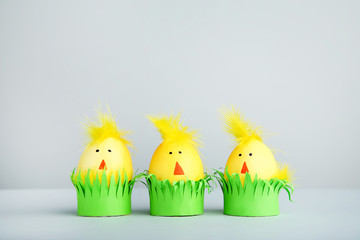 Yellow eggs with funny chicken faces on grey background