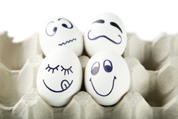 Eggs with funny faces in carton package