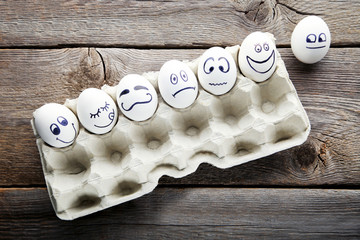 Eggs with funny faces in carton package on wooden table