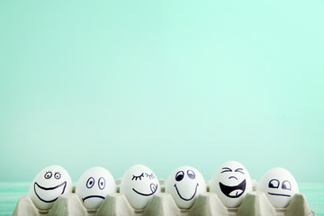 Eggs with funny faces in carton package on mint background