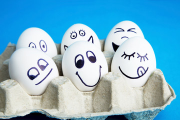 Eggs with funny faces in carton package on blue background