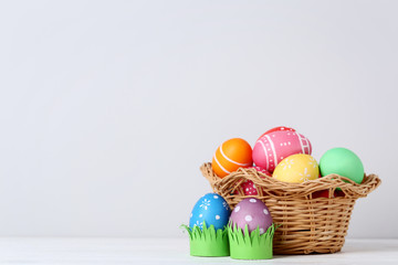 Colorful easter eggs in basket on grey background