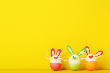 Eggs with funny rabbit faces on yellow background