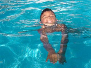 gebräuntes Kind schwimmt in einem Pool