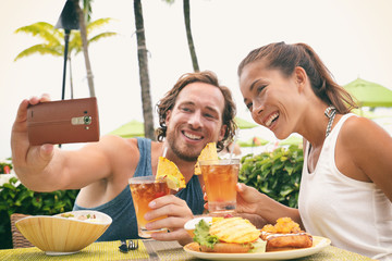 Wall Mural - Selfie photo couple taking picture with phone at Hawaii beach bar on summer vacation. Happy Asian woman and man toasting mai tai drinks at bar having fun. Friends on travel holidays.