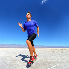 Sport - runner running and sprinting in desert. Athlete man during sprint run at great speed. Fitness man wearing compression clothes.