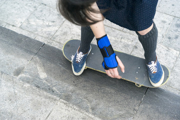 A girl or a woman in a skirt rides on a skateboard in the city, an extreme kind of sport, street sports