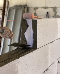 Mason performs an internal masonry blocks aerated concrete. Selective focus