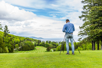 Landscape view of green golf course with hills in summer in La Malbaie, Quebec, Canada in Charlevoix region with photographer and tripod, profession