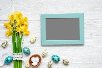 blank photo frame with easter eggs and spring flowers mock up over white wooden table