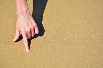 the girl is hand on the sand with place for text