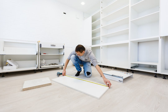 Young man dressed casual assembling furniture in new house