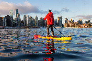 Fotomurales - Adventurous man is paddle boarding near Downtown City during a vibrant winter sunrise. Taken in Coal Harbour, Vancouver, British Columbia, Canada.