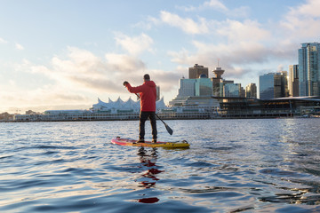 Wall Mural - Adventurous man is paddle boarding near Downtown City during a vibrant winter sunrise. Taken in Coal Harbour, Vancouver, British Columbia, Canada.