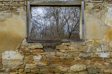 View from a wood window of an old ruin house near the forest.  Wooden frame of rural landscape. Window frame abstract landscape.