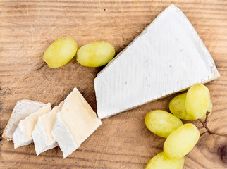 Creamy Brie on rustic  cutting board over white wooden background,