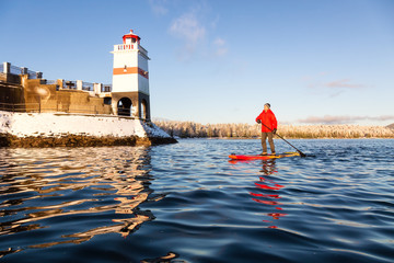 Wall Mural - Man Paddle Barding near Brockton Point Lighthouse in Stanley park during a vibrant winter sunrise. Taken in Downtown Vancouver, British Columbia, Canada.