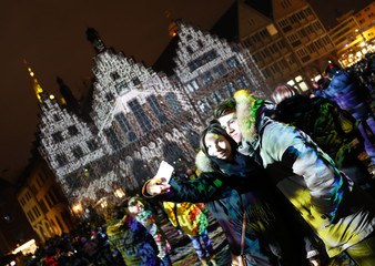 A couple take a selfie in front of illuminated Frankfurt town hall Roemer during the Luminale, light and building event in Frankfurt