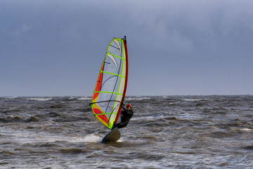 Adventurous man is windsurfing in stormy winter conditions. Taken in Centennial Beach, Delta, Greater Vancouver, British Columbia, Canada.