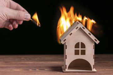 Model house in fire and hand with matchstick on a black background.