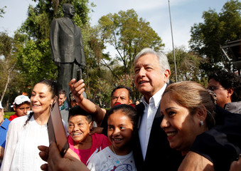 Andres Manuel Lopez Obrador, MORENA's presidential candidate, greets supporters after offering a floral tribute at Lazaro Cardenas monument in Mexico City