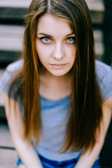 Young girl portrait. Blue eyed brunette female expressive sensual face. Big   sad innocent eyes of adorable woman sitting on wooden stairs outdoor. Reflexive person state of mind. Deep inner mood.