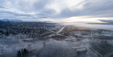 Aerial panoramic view of the residential neighborhood in the city during a foggy sunrise. Taken in New Westminster, Greater Vancouver, British Columbia, Canada.