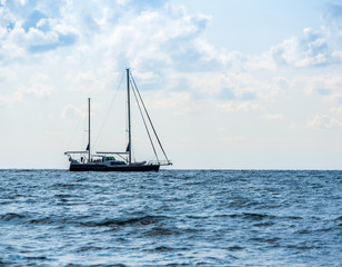 Sailing yacht in the open Sea. Blue water.