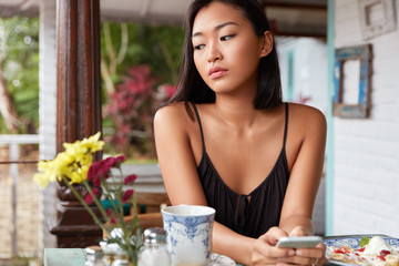 Thoughtful brunette Asian female in casual clothing uses modern cell phone for messaging with friends, spends free time in coffee shop, enjoys tasty dish and hot drink, looks pensively down.