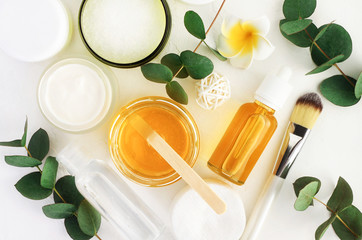 Natural cosmetics ingredients for skincare, body and hair care. Golden honey in jar and green herbal eucalyptus leaves. Top view bottles with facial treatment product white background.
